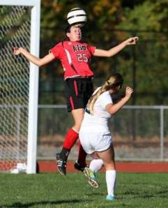 Bishop Ahr's Sarah Harman (left) goes up for a header during the first half of Tuesday's game. Photo by: Mark R. Sullivan